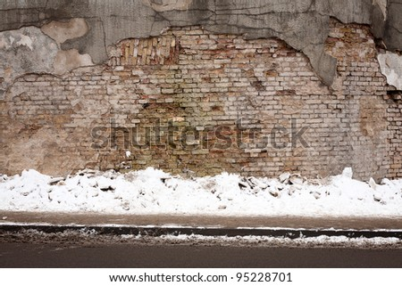 Old weathered wall of bricks and a ground covered with snow - stock photo