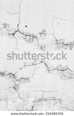 Old weathered wall with white paint peeling off - stock photo