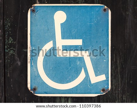 Old weathered wheelchair sign for the handicapped on a black wooden wall - stock photo