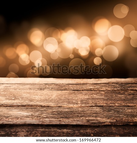 Old weathered wooden board or rustic table top with a sparkling bokeh of golden party lights in the background - stock photo