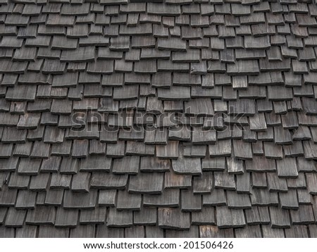 Old weathered wooden shingles continue being used as roofing material. - stock photo
