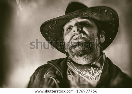 Old West Cowboy Snarl. Old west cowboy snarls in his cowboy hat,  edited in vintage film style. - stock photo