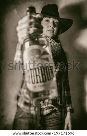 Old West Cowgirl With Bourbon. Old west cowgirl with a bottle of Bourbon, edited in vintage film style. - stock photo