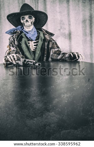 Old West Skeleton Revolver Copy Space. Old west bandit outlaw skeleton at a poker table with a colt 45 pistol revolver edited in vintage film style with copy space. - stock photo