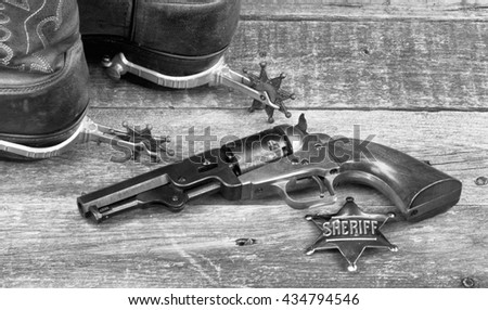 Old western pistol, badge, spurs and cowboy boots in black and white.. - stock photo
