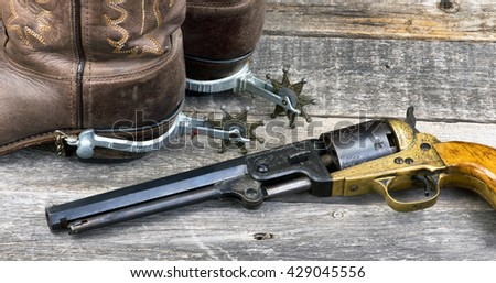 Old western pistol ,spurs and cowboy boots. - stock photo