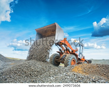old wheel loader excavator loadding gravel  - stock photo