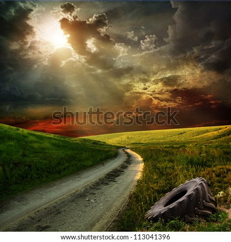old wheel next to a country road at sunset - stock photo