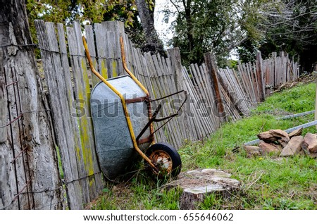Old wheelbarrow leaning up against rickety fence