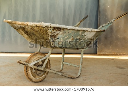 Old wheelbarrow working tools in a construction - stock photo