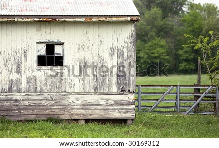 old white barn with window and gate - stock photo