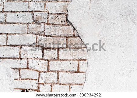 old white brick wall with crumbling plaster - stock photo