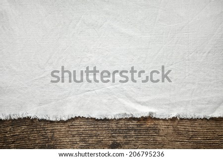 old white cotton tablecloth on wooden table - stock photo