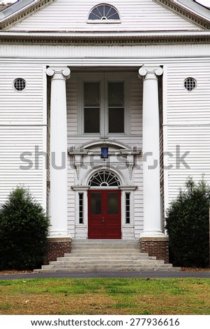 Old white historic home with columns and red door and doorsteps