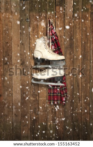 old white ice skates and scarf hanging on a wall - stock photo