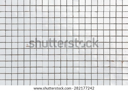 old white obsolete and damaged tiled wall as a texture or background white ceramic tile