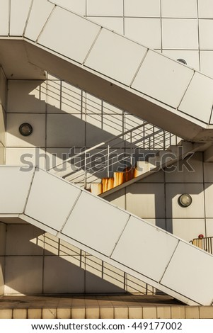 Old white painted metal fire escape of an industrial building with traces of orange streaks of rust. Staircase on the outside of the concrete wall - stock photo