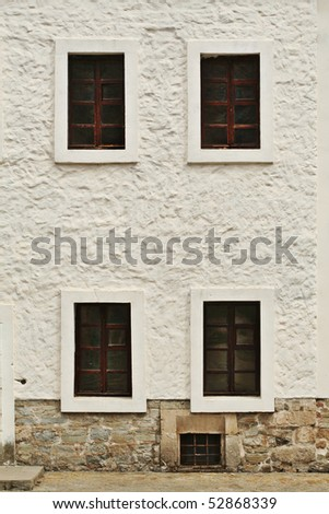 old white wall with dark woden windows - stock photo
