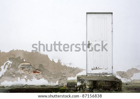 Old white wall with doors and steps - stock photo