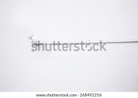 old white water tap and white washed wall - stock photo