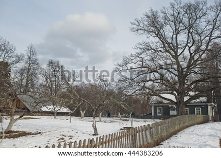 Old white wooden fence leads to the small green house