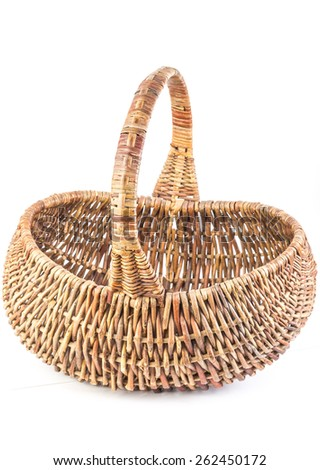 Old wicker basket woven from heavy cane with unique shape and carrying handle.  Vertical format on white background with copy space. - stock photo