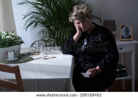 Old widow is worried because of her husband's death - stock photo