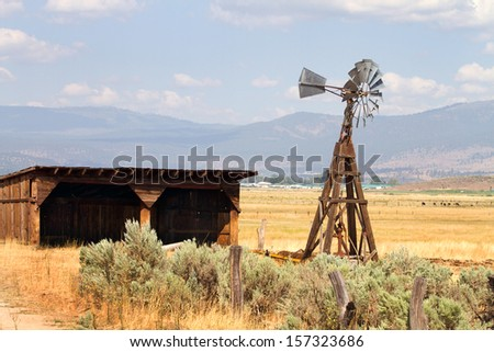 Old wind driven water pumping windmill stands next to an empty storage shed on a cattle ranch in a California mountain valley. - stock photo