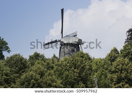 old wind mill behind trees