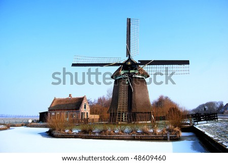 Old wind mill on a river in the Netherlands