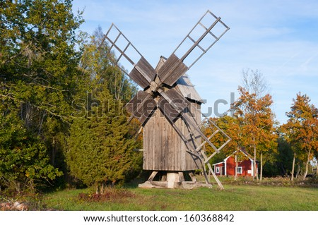 Old windmill an typical red wooden house in Sweden, island Oeland, in rural landscape. - stock photo