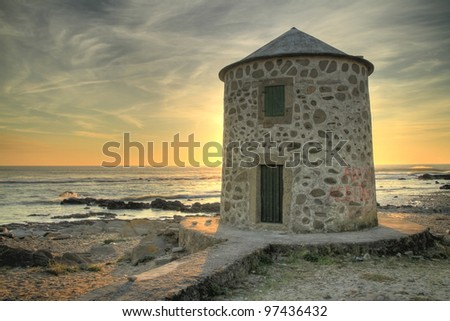Old windmill at sunset on the coast of Viana do Castelo, Portugal (HDR photo) - stock photo