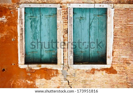 Old window at an abandoned dilapidated house - Closed old shuttered weathered wooden window in the Venice, Italy - stock photo