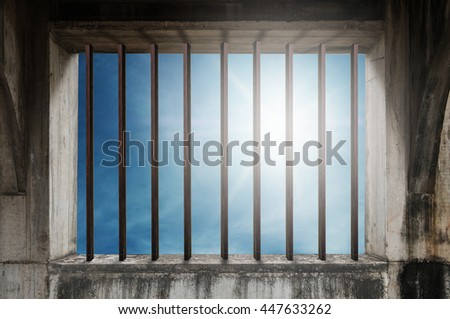old window frame with iron bar in jail and blue sky with bright sunlight