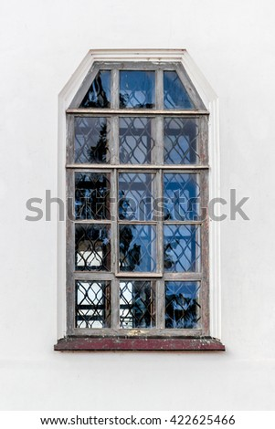 Old window on white facade of the Monastery