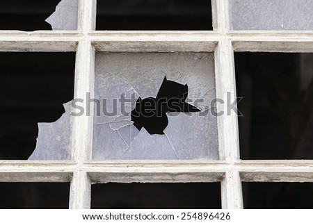 Old window with broken glass, detail of an abandoned factory, ruin and crime - stock photo
