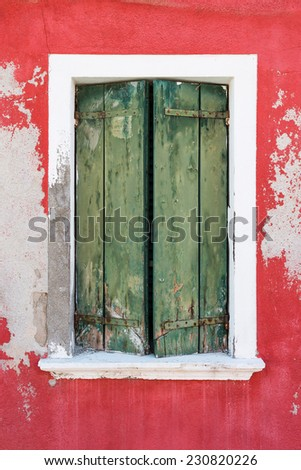 Old window with closed green shutters. Burano. Venice. Italy - stock photo