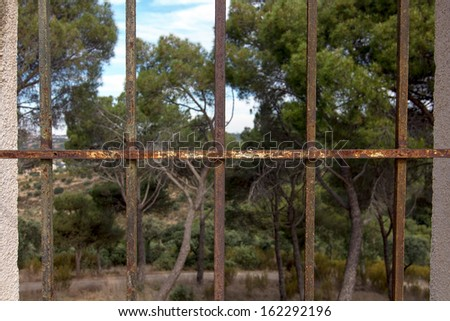 Old window with iron bars at home in ruins - stock photo