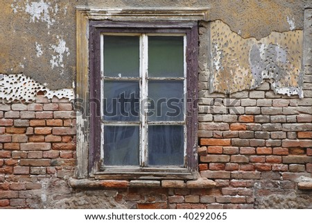 Old window with plaster and brick wall fallen in in ruins in Zagreb, Croatia.