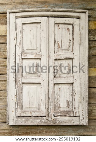 old window with shutters on a wooden wall - stock photo