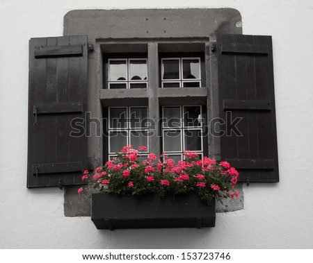Old window with wooden shutters and flower box, Saint Jean Pied de Port, France - stock photo