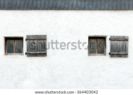 Old windows and shutters in an Austrian castle wall - stock photo
