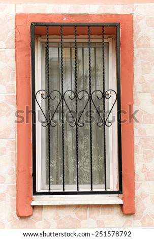 Old windows with ornamented metal lattice. Barred window.. - stock photo