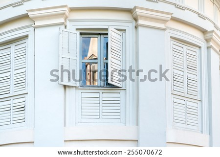 Old windows with shutters on classic building wall  - stock photo