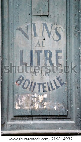 "Old wine and spirit cellar sign. Text in French ""Vins au litre, a la bouteille"" meaning ""Wine selling by liters or in bottles"".  - stock photo"