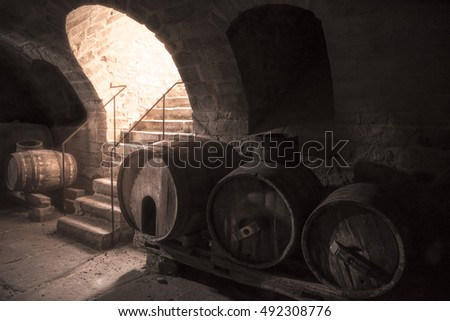 Old wine cellar with wooden barrels and stone stairs - Aged wine cellar interior with old wooden barrels and stone stairs, with strong light coming down through the entrance.