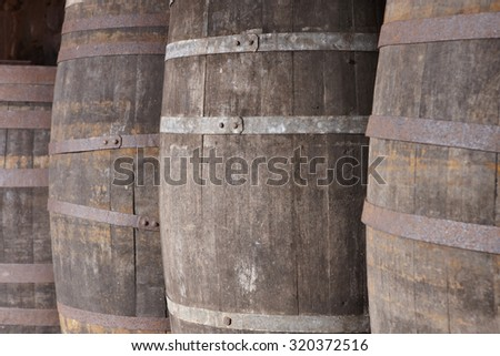 Old wine wooden barrels detail in a winery. Warm tone. Horizontal - stock photo