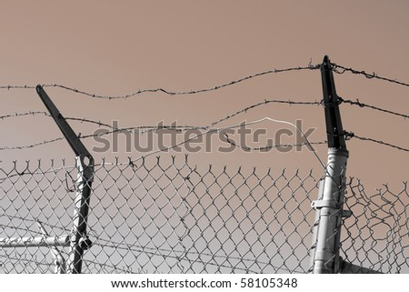 Old wire fence with barbed wire on top.