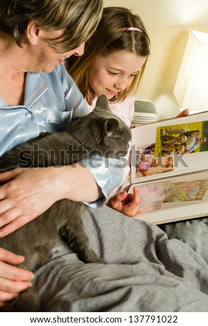 Old woman and granddaughter spending time together looking at pictures - stock photo