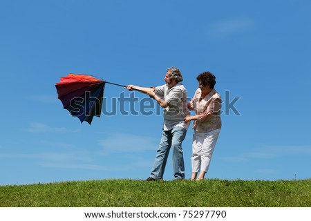 old woman and man standing on summer lawn with multicolored umbrella, wind evert it